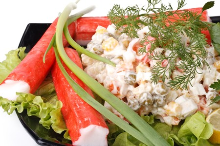 crabmeat: Crabmeat sticks with vegetables and salad on a white background