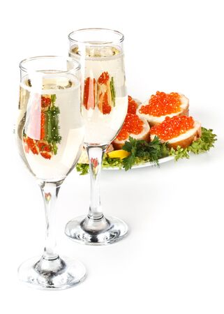 Sandwiches with red caviar and two glasses of champagne on a white background photo