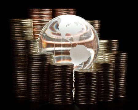 Diagram of growth from coins and glass globe. Global business concept. photo