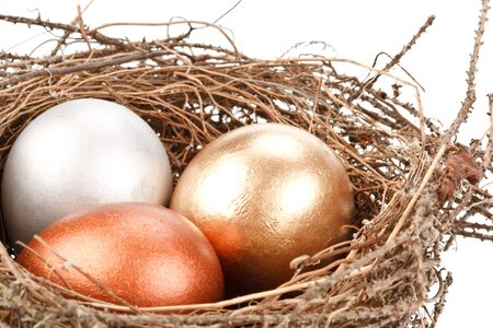 Gold, silver and bronze eggs in a real nest photo
