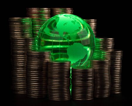 Diagram of growth from coins and green glass globe. Global business concept. photo