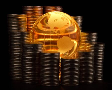 Diagram of growth from coins and yellow glass globe. Global business concept. photo