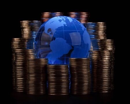 Diagram of growth from coins and blue glass globe. Global business concept. photo