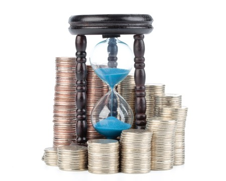 Diagram of growth from coins and hourglass on a white background. Time is money concept. photo