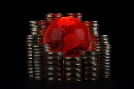 Diagram of growth from coins and red glass globe. Global business concept. photo