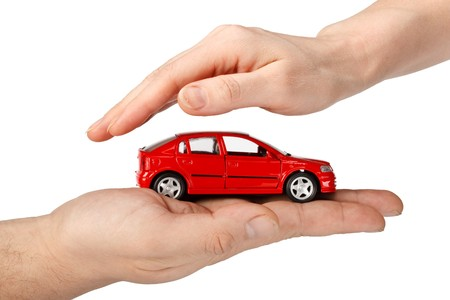 car insurance: Red car in hands on a white background. Concept of safe driving Stock Photo