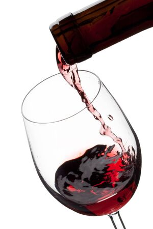 pour: Red wine poured in a glass isolated on a white background
