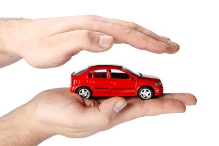 защита: Красный автомобиль в руках на белом фоне. Концепция безопасного вождения Фото со стока