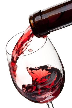 wine pouring: Il vino rosso versato in un bicchiere isolato su uno sfondo bianco Archivio Fotografico
