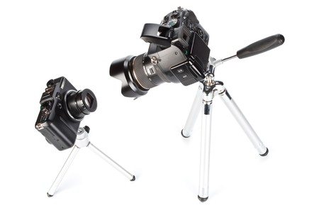Two various modern digital cameras on a white background. Concept for a choice problem photo