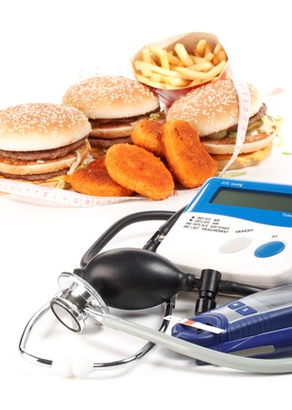 Fast-food, blood pressure meter, stethoscope and glucose meter on a white background photo