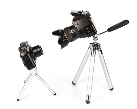 tripod: Two various modern digital cameras on a white background. Concept for a choice problem