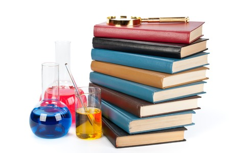 Staircase from books , flasks and a magnifier on a white background photo