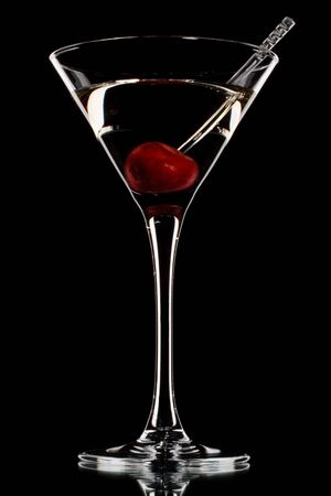 Martini glass with cherry isolated on a black background. Stock Photo