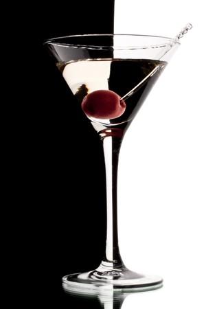 copa de martini: Vaso de martini con cereza aislado en un fondo blanco y negro. Foto de archivo
