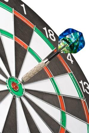 Dart on bulls eye of a dartboard. Close up. Stock Photo