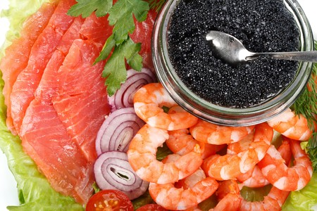 Black caviar, tiger shrimps and a salty trout with vegetables on a white background Stock Photo - 4556824