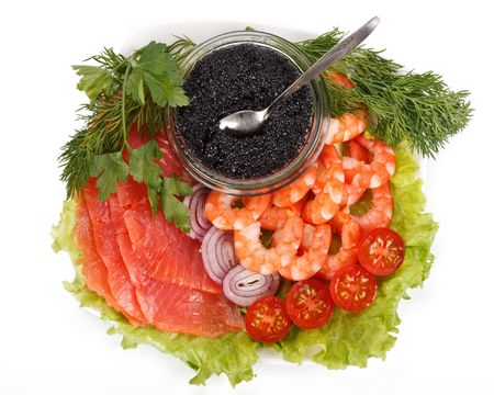 Black caviar, tiger shrimps and a salty trout with vegetables on a white background photo