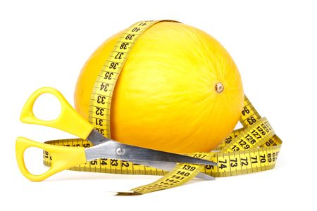 Melon, scissors and measuring tape. Close up photo