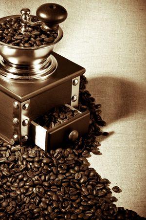 molinillo: Antiguo molinillo de caf� y granos de caf� sobre un fondo en un saco