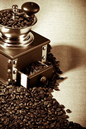 Old-fashioned coffee grinder and coffee beans on a on a sack background photo