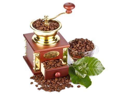 Old-fashioned coffee grinder, coffee beans and green leaves on a white background