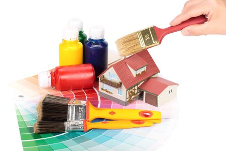 Various painting tools, miniature house and color guide on a white background photo