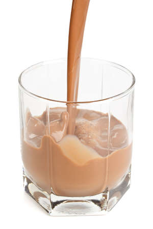 Chocolate milk pouring in a glass on a white background