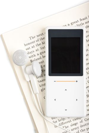 earbud: Modern MP3 player and  book. Audiobook concept. Close up.