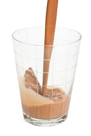 Chocolate milk pouring in a glass on a white background photo