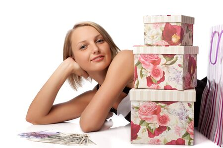 Pretty woman with shopping bags, gift boxes and money on a white background photo