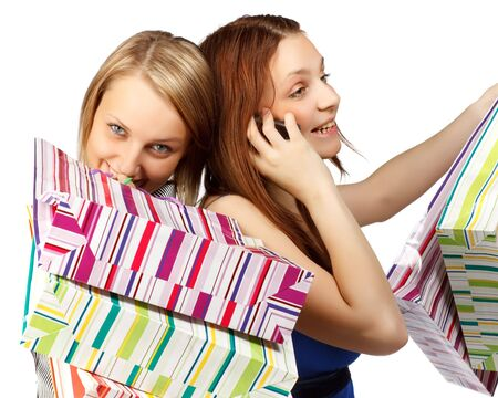 Two pretty girls discuss purchases by mobile phone on a white background photo