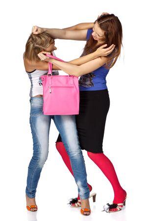 Dos niñas quitarle uno al otro una bolsa. Venta.