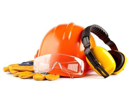 Oranje helm, oordopjes, veiligheidsbril en handschoenen op een witte achtergrond Stockfoto