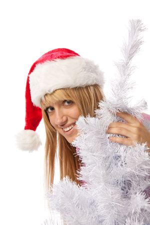 The beautiful girl in a Santa's cap sits near a Christmas tree on a white background. Stock Photo - 5528016