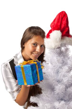 The beautiful girl with a gift in a Santa's cap sits near a Christmas tree on a white background. Stock Photo - 5563836