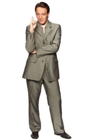 specifies: The young businessman in a suit specifies a finger upwards over white background