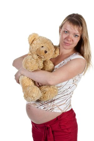 The pregnant woman with a teddy bear on a white background
