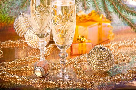 Decoration with an firtree branch, gift boxes, christmas baubles and champagne glasses photo