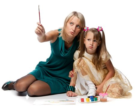 Young mum with a daughter draw a picture paints on a white background. photo