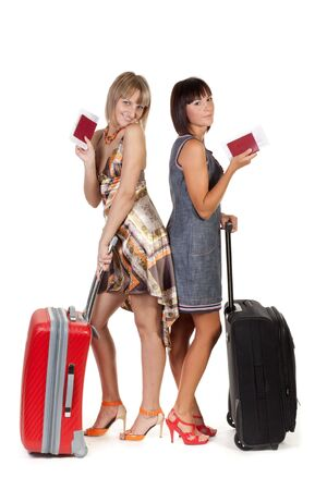 Two nice girls with suitcases on a white background photo