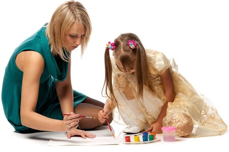Young mum with a daughter draw a picture paints on a white background. Stock Photo - 5619525