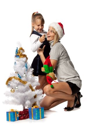 The nice girl with mum decorates a Christmas tree on a white background. photo
