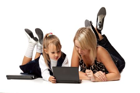 Mum with a daughter lay with the laptop on a white background. photo