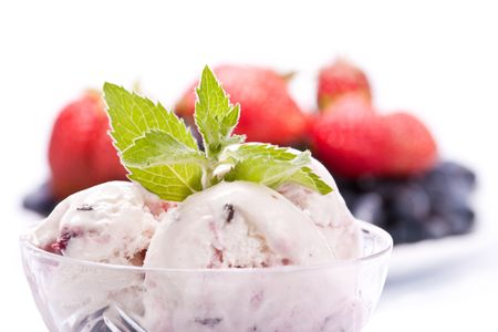 Ice-cream with fresh berries of a strawberry and a honeysuckle on a white background. photo