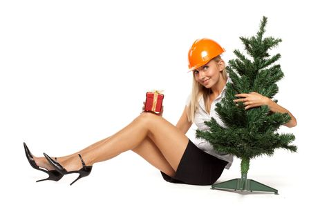 Female construction worker with gift box sits near a Christmas tree on a white background. photo