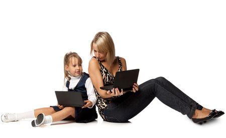 The girl and mother sit a back to each other with laptops on a white background. photo