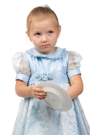 The little girl diligently washes with a sponge a plate on a white background. The mums assistant. photo