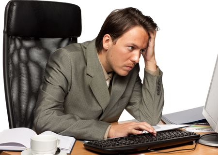 computer frustration: Stressed businessman looking at computer on a white background