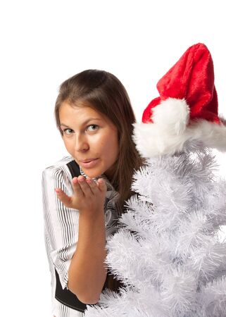The beautiful girl in a Santas cap sits near a Christmas tree and sends an air kiss on a white background. photo